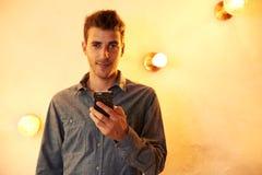 Netter junger Mann, der mit Mobiltelefon aufwirft Lizenzfreies Stockbild