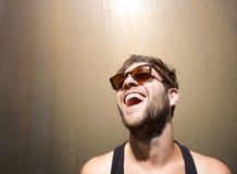 Netter junger Mann, der mit Sonnenbrille lacht Lizenzfreie Stockfotografie