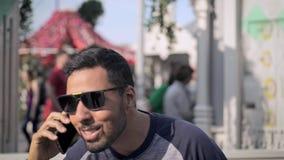 Netter junger Mann in der Sonnenbrille draußen sprechend am Telefon stock video footage
