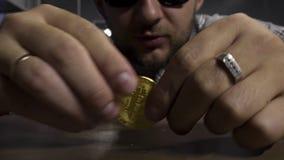 Netter junger Mann in der Sonnenbrille spinnt gro?e neue Gold-bitcoin M?nze auf brauner Tabelle stock footage