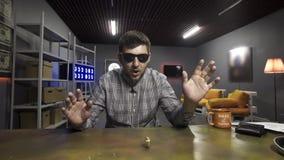 Netter junger Mann in der Sonnenbrille spinnt gro?e neue Gold-bitcoin M?nze auf brauner Tabelle stock video footage