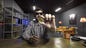 Netter junger Mann in der Sonnenbrille spricht und zeigt gro?es neues Gold-bitcoin an der Kamera stock footage