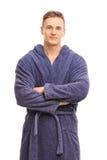 Netter junger Mann in einem blauen Bademantellächeln lizenzfreies stockfoto