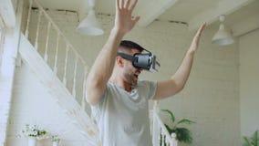 Netter junger Mann haben Spaß und tanzen beim Erfahrung unter Verwendung 360 VR-Kopfhörergläser virtueller Realität herein erhalt stock video