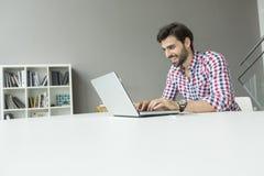 Netter junger Mann im Büro Stockbilder
