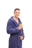 Netter junger Mann im Bademantel, der einen Saft hält Lizenzfreie Stockfotografie