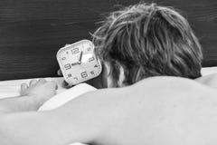 Netter junger Mann wacht auf, nachdem er morgens geschlafen hat Junger ausdehnender Mann beim morgens aufwachen stockfotografie
