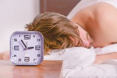 Netter junger Mann wacht auf, nachdem er morgens geschlafen hat Bemannen Sie glaubenden hinteren Schmerz im Bett, nachdem Sie ges lizenzfreie stockfotos