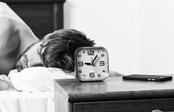 Netter junger Mann wacht auf, nachdem er morgens geschlafen hat F??e des Mannes schlafend im bequemen Bett Aufwachen der Ebene lizenzfreie stockbilder