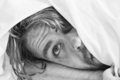 Netter junger Mann wacht auf, nachdem er morgens geschlafen hat Gut aussehender Mann, der Uhr im Bett nachdem dem Aufwachen in ve lizenzfreie stockfotos