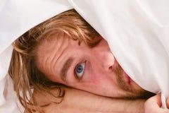 Netter junger Mann wacht auf, nachdem er morgens geschlafen hat Gut aussehender Mann, der Uhr im Bett nachdem dem Aufwachen in ve stockfoto