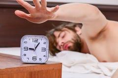 Netter junger Mann wacht auf, nachdem er morgens geschlafen hat Gut aussehender Mann, der Uhr im Bett nachdem dem Aufwachen in ve stockfotografie