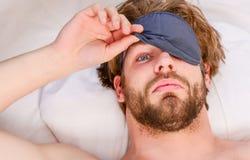 Netter junger Mann wacht auf, nachdem er morgens geschlafen hat Schließen Sie oben von den Füßen in einem Bett unter weißer Decke lizenzfreie stockfotografie