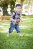 Netter junger Mischrasse-Junge, der draußen Fußball spielt Stockfotos