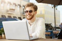 Netter junger roter behaarter männlicher freiberuflich tätiger Designer im weißen Hemd und in der Sonnenbrille mit Ohrringlächeln lizenzfreie stockfotografie