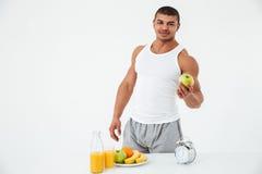 Netter junger Sportler, der Apfel hält Betrachten der Kamera stockbild