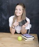 Netter junger Student nahe Tafel mit Kopienbuch-Taschenrechnerstift, Kopienraum Stockfoto