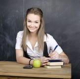 Netter junger Student nahe Tafel mit Kopienbuch-Taschenrechnerstift, Kopienraum Lizenzfreies Stockbild