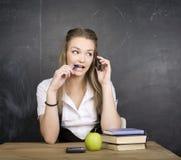 Netter junger Student nahe Tafel mit Kopienbuch-Taschenrechnerstift, Kopienraum Stockfotografie