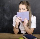 Netter junger Student nahe Tafel mit Kopienbuch-Taschenrechnerstift, Kopienraum Stockfotos