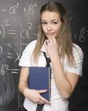 Netter junger Student nahe Tafel mit Kopienbuch-Taschenrechnerstift, Kopienraum Lizenzfreie Stockfotografie