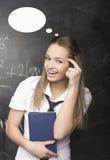 Netter junger Student nahe Tafel mit Kopienbuch-Taschenrechnerstift, Kopienraum Lizenzfreie Stockfotos