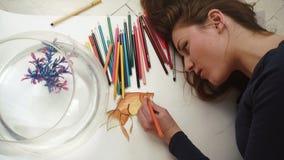 Netter junger weiblicher Künstler macht ein Bild von nahem hohem der kleinen goldenen Fische Beschneidungspfad eingeschlossen stock video footage