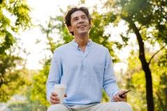 Netter junger zufälliger Mann, der Handy verwendet stockbild