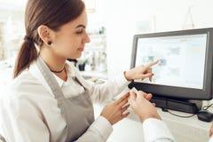 Netter Kassierer, der digitales Gerät für Zahlung verwendet stockfotos