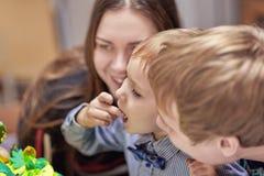 Netter kaukasischer blonder Junge isst Herzchen vom Geburtstagskuchen, der zwischen den Eltern sitzt lizenzfreie stockfotografie