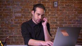 Netter kaukasischer Geschäftsmann, der am Telefon hängt und den Laptop während betrachtet das Sitzen konzentriert, an Arbeitsschr stock footage