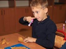 Netter kaukasischer Junge, der Grundschüler, der bei Tisch mit mit sitzt, handcraft Er hob seine Hand an lizenzfreie stockfotografie
