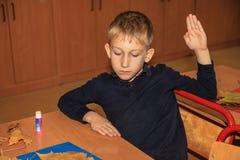 Netter kaukasischer Junge, der Grundschüler, der bei Tisch mit mit sitzt, handcraft Er hob seine Hand an lizenzfreie stockfotos