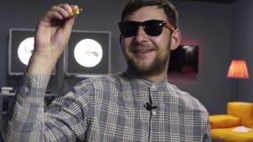 Netter Kerl Blogger h?lt gro?es Gold-bitcoin in der Hand und Blicke an der Kamera mit L?cheln stock footage