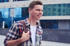 Netter Kerl hört Musik beim Gehen in das Stadtzentrum Lizenzfreie Stockfotografie
