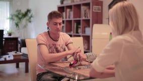 Netter Kerl sitzt mit jungen Blondinen bei Tisch mit kleinem Nano-Hubschrauber auf ihm stock video footage