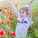 Netter Kinderjunge mit Mohnblumenblume auf Mohnblumenfeld am warmen Sommertag Lizenzfreies Stockfoto