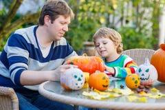 Netter Kinderjunge und sein Vater, die Steckfassung-Olaterne für Halloween herstellt Stockfotografie