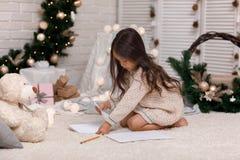 Netter Kindermädchen-Schreibensbuchstabe zu Santa Claus zu Hause stockbild
