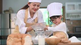 Netter kleiner asiatischer Junge und schöne Mutter, die Teigmehl mit Filtersiebsieb in der Hauptküche auf Tabelle für siebt, zu s stock footage