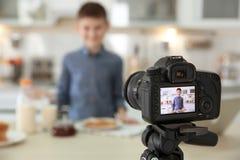 Netter kleiner Blogger mit Lebensmittel auf Kameraschirm, Stockfoto
