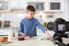 Netter kleiner Blogger mit Lebensmittelaufnahmevideo Lizenzfreie Stockfotografie