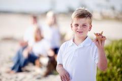 Netter kleiner blonder Junge, der seine Starfish vorführt Stockbilder