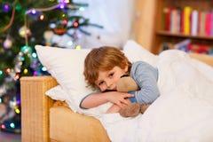 Netter kleiner blonder Junge in seinem Bett nahe Weihnachtsbaum mit Lichtern Stockbild