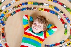 Netter kleiner blonder Kinderjunge, der mit vielen Spielzeugautos Innen spielt Stockfotos