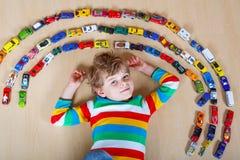 Netter kleiner blonder Kinderjunge, der mit vielen Spielzeugautos Innen spielt Lizenzfreies Stockbild