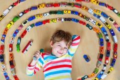 Netter kleiner blonder Kinderjunge, der mit vielen Spielzeugautos Innen spielt Stockbild