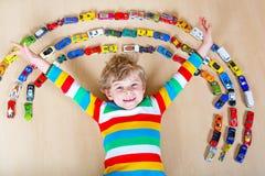 Netter kleiner blonder Kinderjunge, der mit vielen Spielzeugautos Innen spielt Lizenzfreie Stockbilder