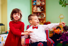 Netter kleiner Herr im Rollstuhl und in Dame an den Feiertagen im Kindergarten für Kinder mit speziellem Bedarf stockfotografie