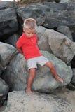 Netter kleiner Junge auf den Felsen Stockfotografie